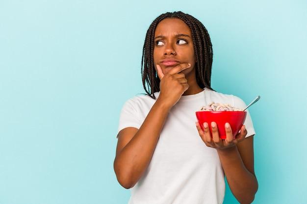 疑わしいと懐疑的な表現で横向きに見える青い背景に分離されたシリアルのボウルを保持している若いアフリカ系アメリカ人の女性。