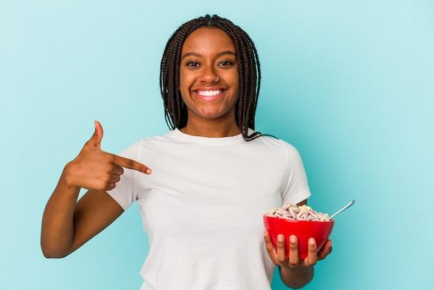 誇りと自信を持って、シャツのコピースペースを手で指している青い背景の人に分離されたシリアルのボウルを保持している若いアフリカ系アメリカ人女性 Premium写真