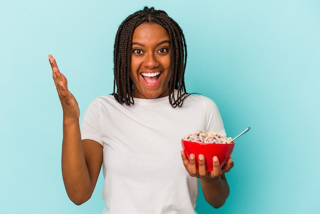青い背景に分離されたシリアルのボウルを保持している若いアフリカ系アメリカ人の女性は、嬉しい驚きを受け取り、興奮し、手を上げます。