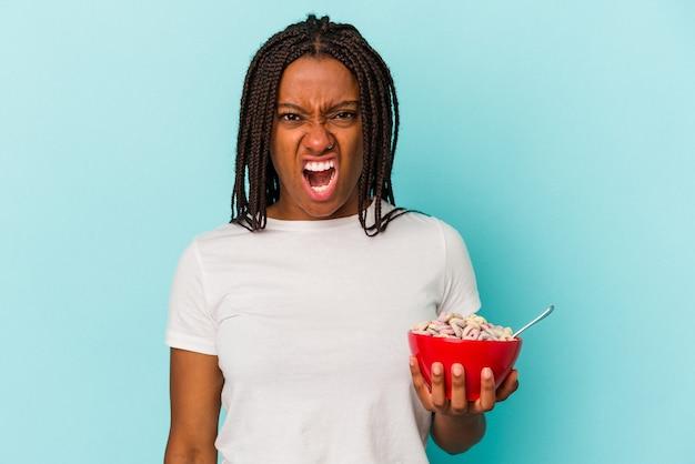 非常に怒って攻撃的に叫んで青い背景に分離されたシリアルのボウルを保持している若いアフリカ系アメリカ人の女性。