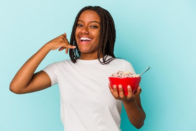 指で携帯電話の呼び出しジェスチャーを示す青い背景に分離されたシリアルのボウルを保持している若いアフリカ系アメリカ人の女性。