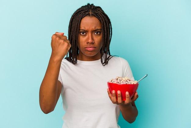 파란색 배경에 격리된 시리얼 한 그릇을 들고 카메라에 주먹을 대는 젊은 흑인 여성, 공격적인 표정.