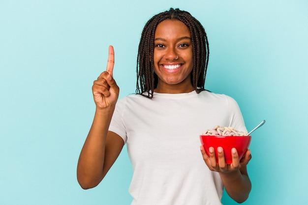 指でナンバーワンを示す青い背景に分離されたシリアルのボウルを保持している若いアフリカ系アメリカ人の女性。