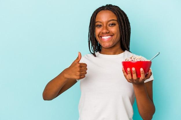 笑顔と親指を上げる青い背景に分離されたシリアルのボウルを保持している若いアフリカ系アメリカ人女性