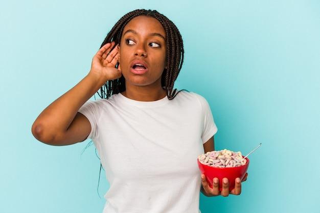 ゴシップを聴こうとしている青い背景に分離されたシリアルのボウルを保持している若いアフリカ系アメリカ人の女性。