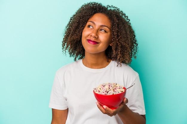 目標と目的を達成することを夢見て青い背景に分離されたシリアルのボウルを保持している若いアフリカ系アメリカ人女性