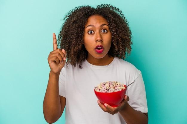 アイデア、インスピレーションの概念を持っている青い背景に分離されたシリアルのボウルを保持している若いアフリカ系アメリカ人女性。 Premium写真