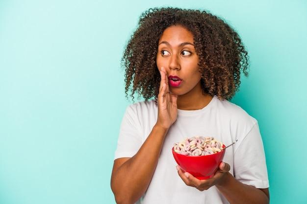 青い背景で隔離のシリアルのボウルを保持している若いアフリカ系アメリカ人の女性は、秘密の熱いブレーキングニュースを言って脇を見ています