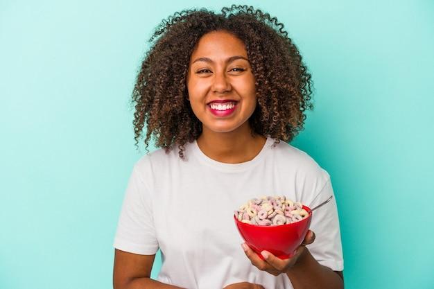 笑って楽しんで青い背景に分離されたシリアルのボウルを保持している若いアフリカ系アメリカ人女性。
