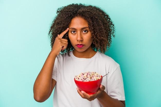 指で寺院を指して、青い背景に分離されたシリアルのボウルを保持している若いアフリカ系アメリカ人の女性は、タスクに焦点を当てて考えています。