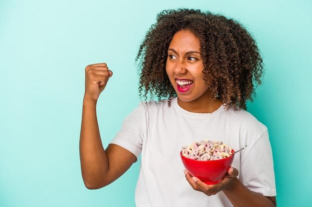 勝利、勝者の概念の後に拳を上げる青い背景に分離されたシリアルのボウルを保持している若いアフリカ系アメリカ人の女性。