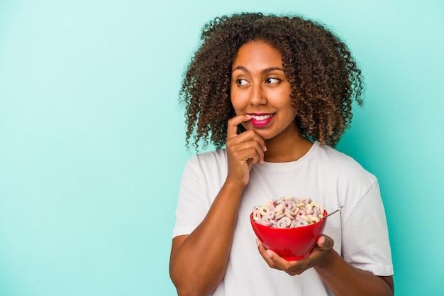 青い背景に分離されたシリアルのボウルを保持している若いアフリカ系アメリカ人の女性は、コピースペースを見ている何かについて考えてリラックスしました。