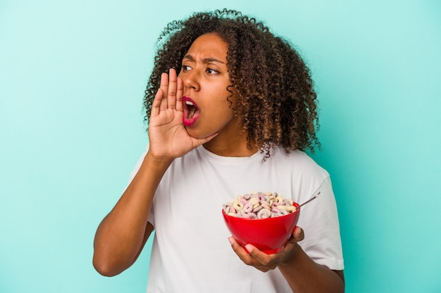 開いた口の近くで叫び、手のひらを保持している青い背景に分離されたシリアルのボウルを保持している若いアフリカ系アメリカ人の女性。