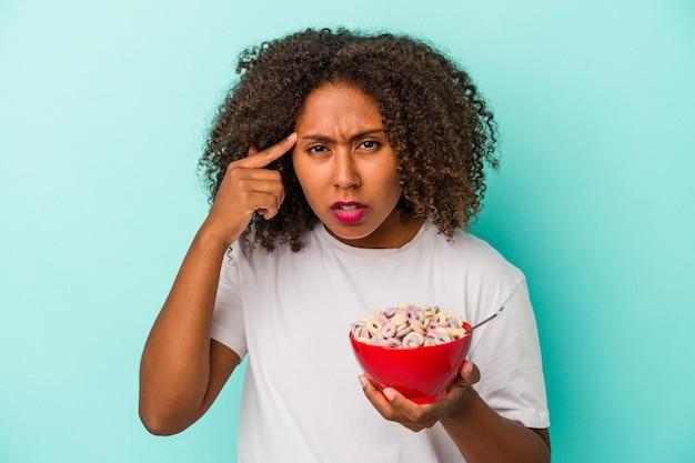 人差し指で失望のジェスチャーを示す青い背景に分離されたシリアルのボウルを保持している若いアフリカ系アメリカ人の女性。
