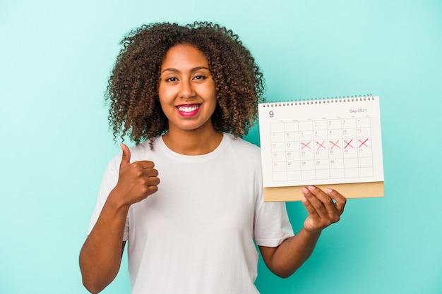 Молодая афро-американская женщина, держащая календарь на синем фоне, улыбается и поднимает палец вверх
