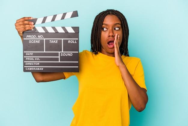 Молодая афро-американская женщина, держащая хлопушку, изолированную на синем фоне, говорит секретные горячие новости о торможении и смотрит в сторону