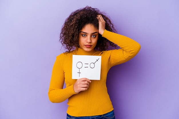 紫色の壁に隔離された男女共同参画のプラカードを持っている若いアフリカ系アメリカ人女性はショックを受け、重要な出会いを思い出しました。