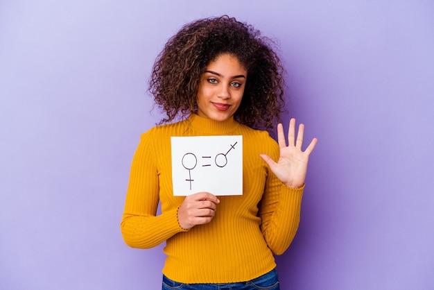 紫色の壁に隔離された男女共同参画のプラカードを持っている若いアフリカ系アメリカ人の女性は、指で5番を示して陽気に笑っています。