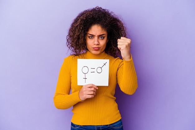 孤立した男女平等のプラカードを保持している若いアフリカ系アメリカ人女性