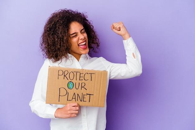 勝利、勝者の概念の後に拳を上げる紫色の壁に分離された女の子のパワープラカードを保持している若いアフリカ系アメリカ人の女性。