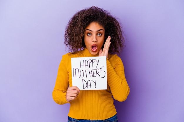 幸せな母の日のプラカードを持っている若いアフリカ系アメリカ人の女性は、驚いてショックを受けました。