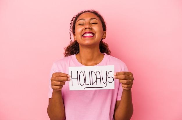 ピンクの背景で隔離の休日のプラカードを保持している若いアフリカ系アメリカ人女性