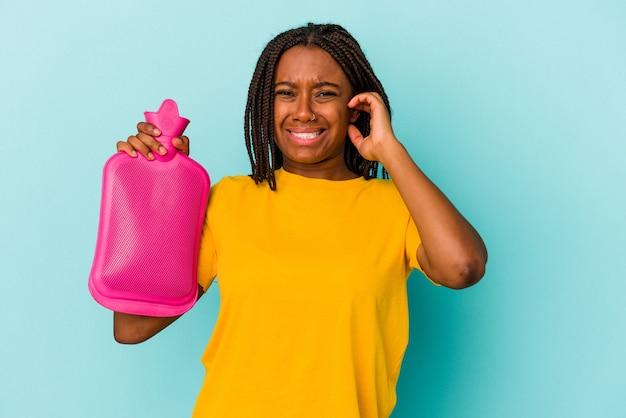 Молодая афро-американская женщина, держащая мешок с горячей водой, изолирована на синем фоне, закрывая уши руками.