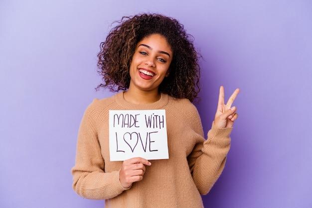 紫色の壁に隔離された愛のプラカードを持っている若いアフリカ系アメリカ人の女性は、指で平和のシンボルを喜んで気楽に示しています。