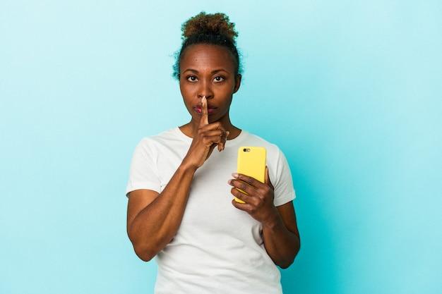 Молодая афро-американская женщина, держащая мобильный телефон, изолированная на синем фоне, хранящая в секрете или просящая молчания.