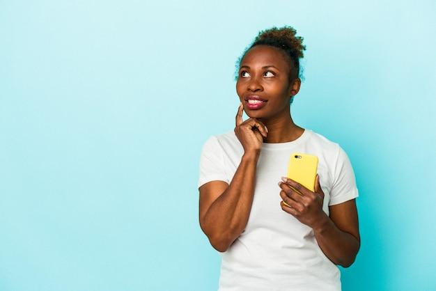 파란색 배경에 격리된 휴대전화를 들고 있는 젊은 아프리카계 미국인 여성은 복사 공간을 보고 있는 무언가에 대해 편안하게 생각하고 있습니다.