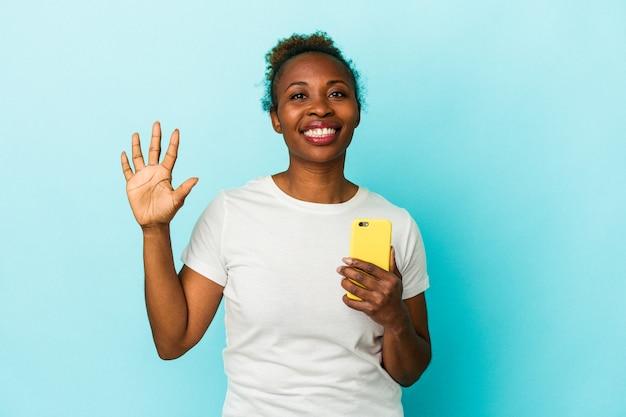 青い背景に分離された携帯電話を持っている若いアフリカ系アメリカ人の女性は、指で5番目を示す陽気な笑顔を浮かべています。