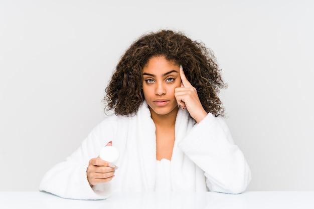Молодая афро-американская женщина, держащая увлажняющий крем, указывая пальцем на висок, думает, сосредоточена на задаче.