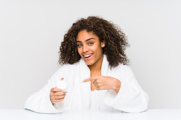 人差し指で離れて元気に指している笑顔の保湿剤を保持している若いアフリカ系アメリカ人女性。