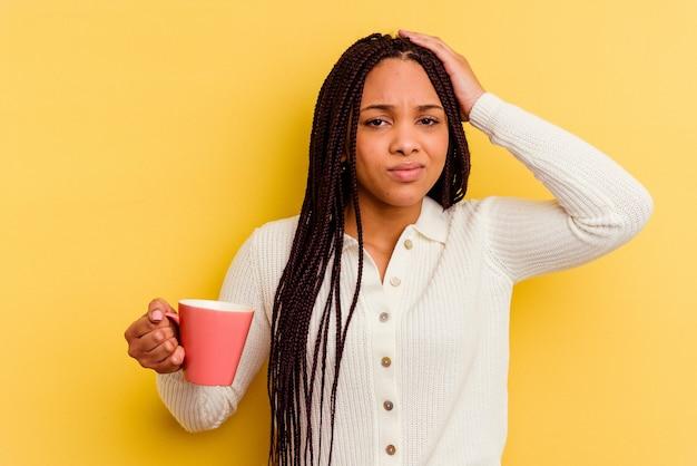 Молодая афро-американская женщина, держащая изолированную кружку в шоке, вспомнила важную встречу.