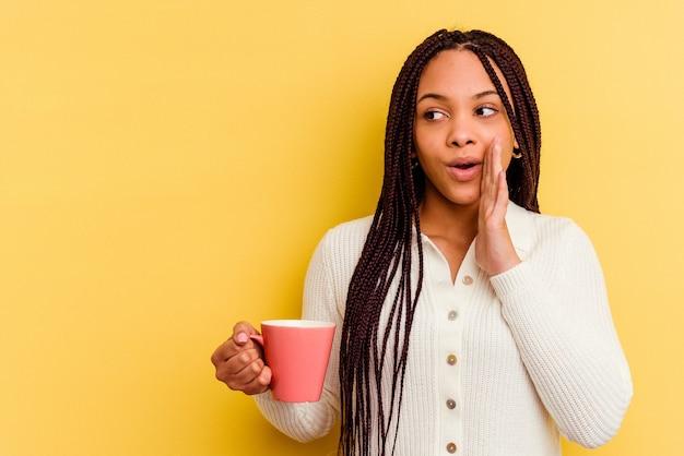고립 된 찻잔을 들고 젊은 아프리카 계 미국인 여자는 비밀 뜨거운 제동 뉴스를 말하고 옆으로보고