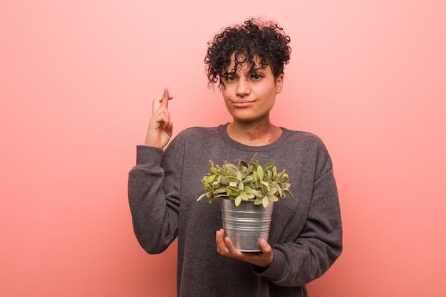 運を持っているために指を交差させる植物を保持している若いアフリカ系アメリカ人の女性