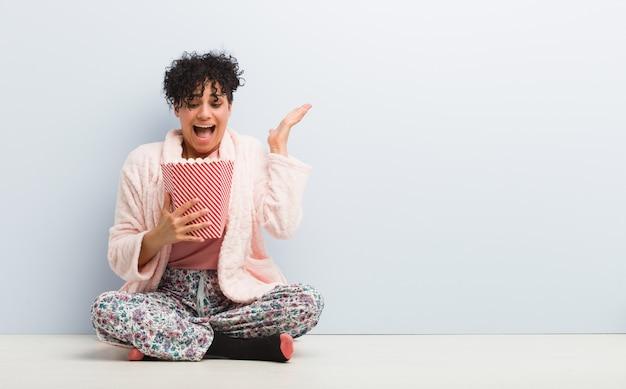 Молодая афро-американская женщина держа ведро попкорна празднуя победу