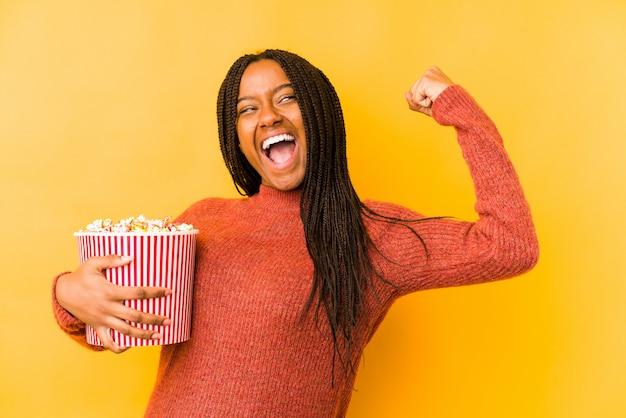 Молодая афро-американская женщина держа кулак повышения попкорна после победы