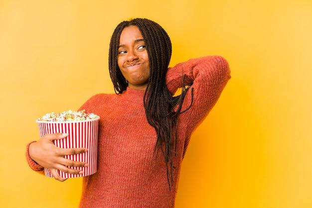 Молодая афро-американская женщина держа попкорн касаясь задней части головы, думая и делая выбор.