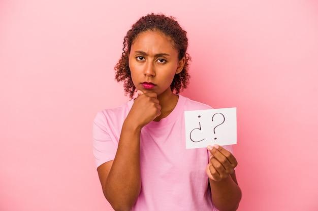 분홍색 배경에 격리된 질문 현수막을 들고 있는 젊은 아프리카계 미국인 여성