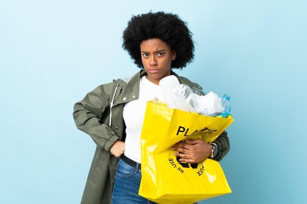 화려한 화가에 고립 된 재활용 가방을 들고 젊은 아프리카 계 미국인 여자