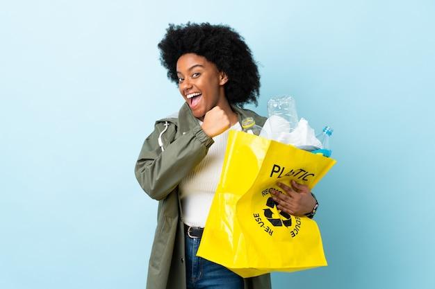 Молодая афро-американская женщина, держащая мешок для мусора, изолированные на красочном фоне, празднует победу