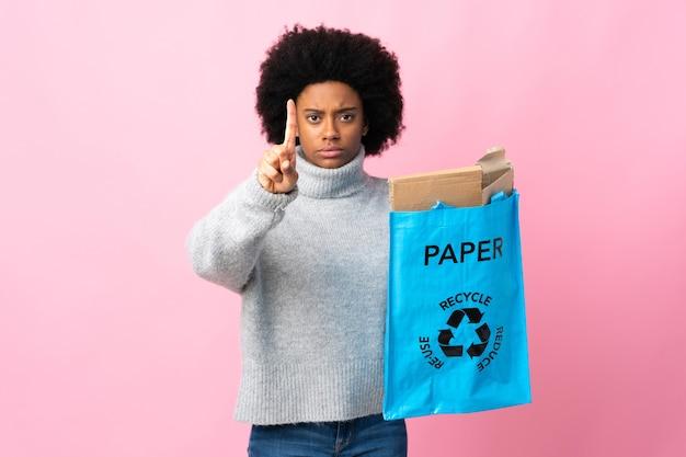 심각한 표정으로 하나를 세는 화려한 배경에 고립 된 재활용 가방을 들고 젊은 아프리카 계 미국인 여자