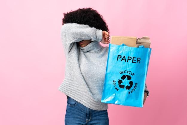 Молодая афроамериканская женщина, держащая мусорный мешок, изолирована на красочном фоне, прикрывая глаза руками