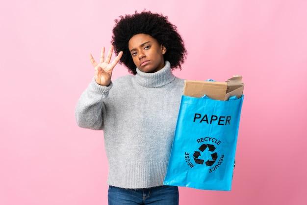 カラフルな背景の幸せと指で4つを数える上に分離されてリサイクルバッグを保持している若いアフリカ系アメリカ人女性