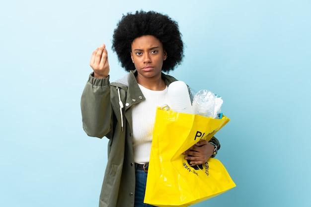 이탈리아 제스처를 만드는 화려한 배경에 고립 된 재활용 가방을 들고 젊은 아프리카 계 미국인 여자