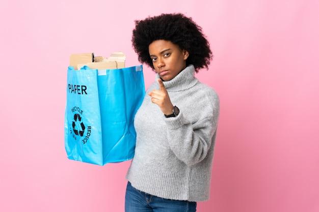 다채로운 좌절에 고립 된 앞을 가리키는 재활용 가방을 들고 젊은 아프리카 계 미국인 여자