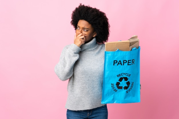 Молодой афроамериканец женщина, держащая рециркуляции мешок, изолированные на красочные с сомнениями и с выражением лица смутить