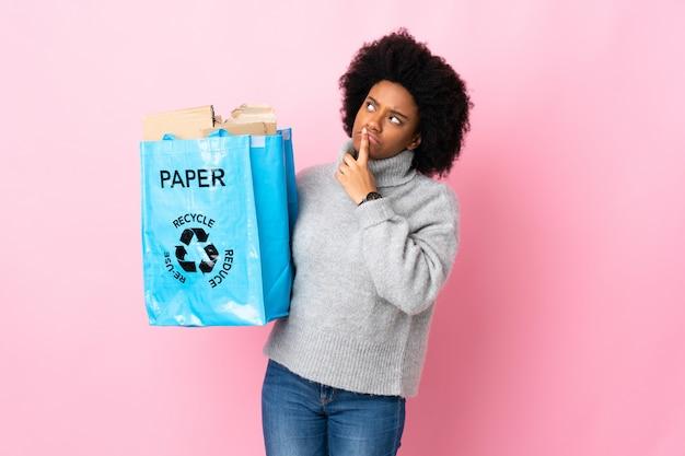 Молодая афро-американская женщина держа сумку рециркулировать изолированную на красочном имеющ сомнения пока смотрящ вверх