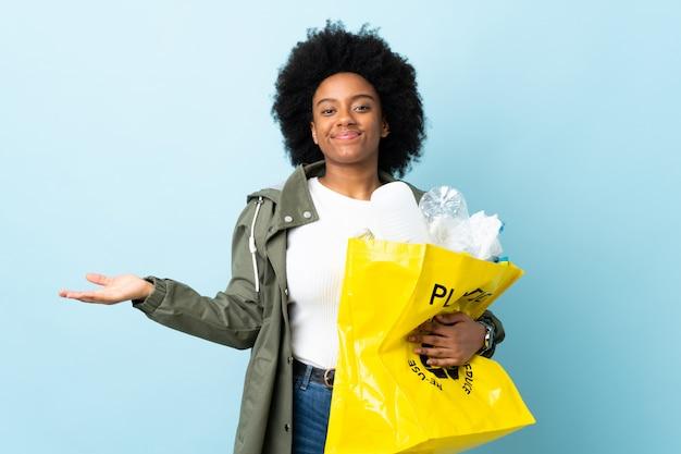 Молодая афро-американская женщина держа сумку рециркулировать изолированную на красочном имеющ сомнения